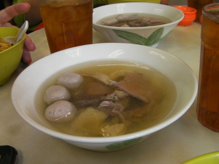 bowl of broth and several types of beef meat