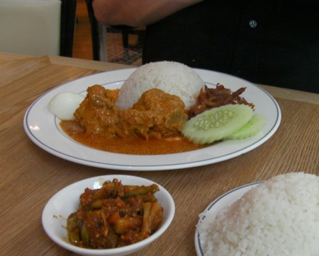 plate containing rice, curry chicken, spicy anchovies, cucumbers, a hard boiled egg and spicy pickles