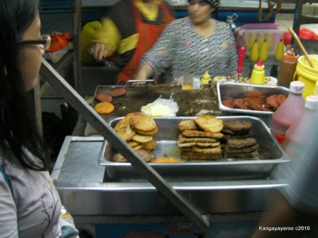burgers being fried with egg and cheese