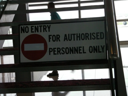 """sign on stairs in airport stating """"no entry for authorized personnel only"""""""