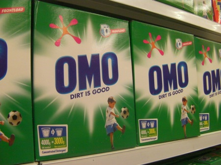 "OMO detergent boxes with tag line ""Dirt is good."""