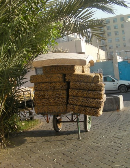 furniture cushions piled high on a hand cart