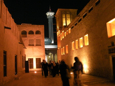 people walking through traditional Arab buildings toward a mosque