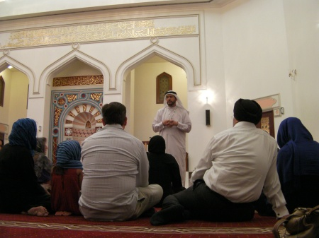 people sitting on the floor inside a mosque