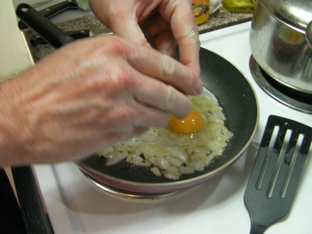 eggs being added to sauteed onions