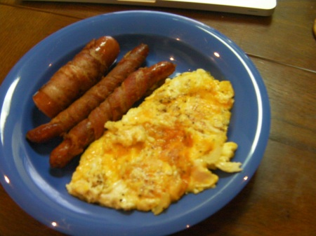 finished bacon wrapped sausage with scrambled cheesy eggs