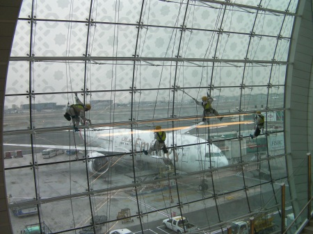 four mean using climbing equipment to clean large airport windows