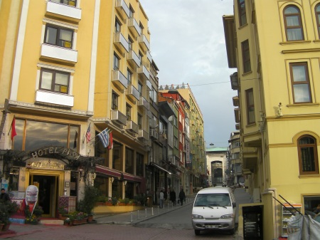 cobblestone street with yellow buildings on both sides