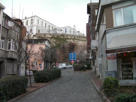 modern street ending at an ancient wall