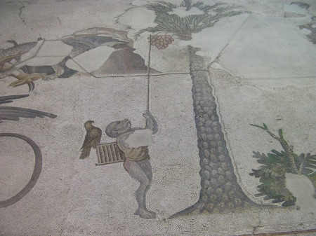 mosaic monkey with stick attempting to catch birds in a tree