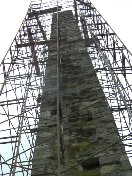large stone column structure surrounded by scaffolding