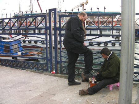 man shining another man's shoes