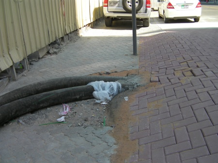 large black pipes entering side of the speed bump made of bricks