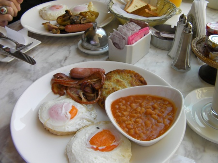 plate of 2 eggs, bacon, potato cake and bowl of beans