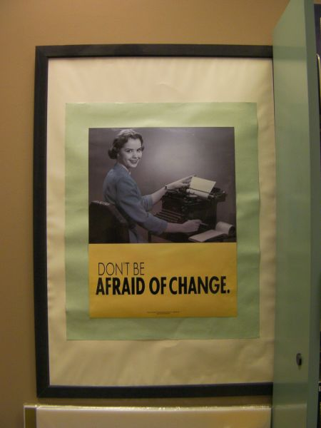 "framed poster showing a black and white photo of a woman using a typewriter with the caption ""don't be afraid of change"""
