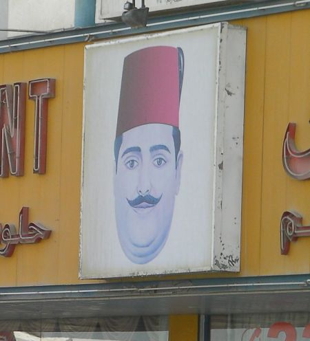 sign showing a man's head wearing a fez hat