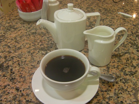 coffee pot, cream pitcher and coffee cup full of very dark coffee