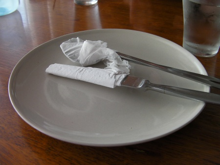 silverware wrapped in paper napkins