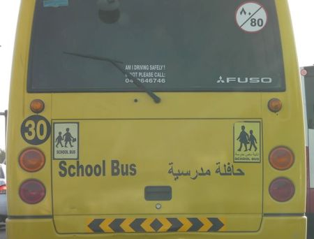 """two """"caution: children"""" signs on a single bus"""