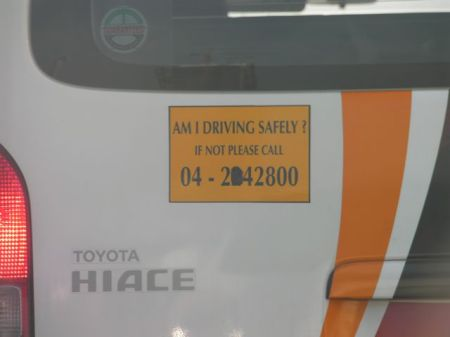 vehicle drive safely sign with an incomplete phone number