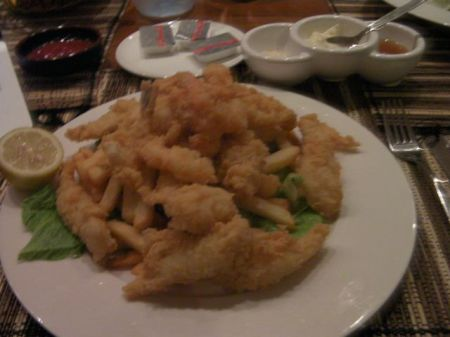 plate piled with french fries and batter fried seafood