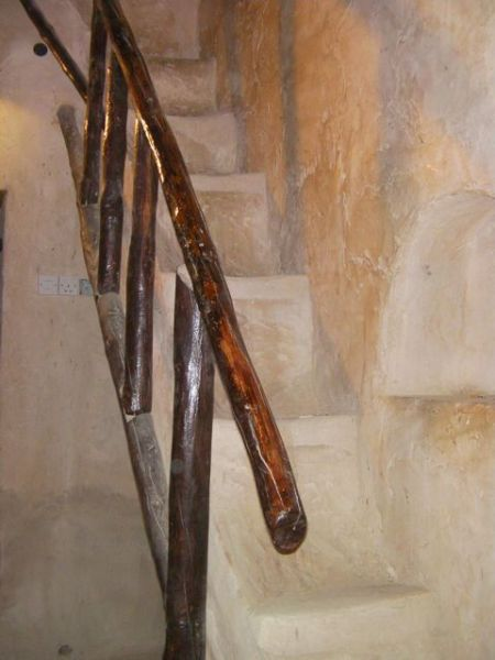 very narrow stairs with a lodge pole handrail