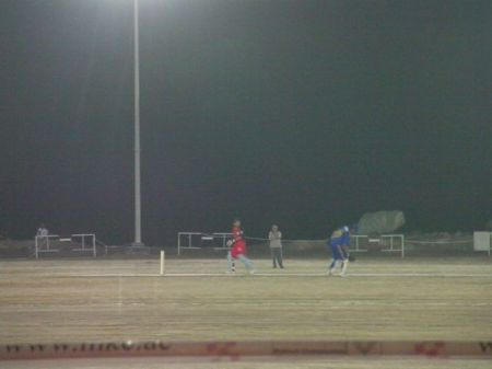 cricket players on a lit field