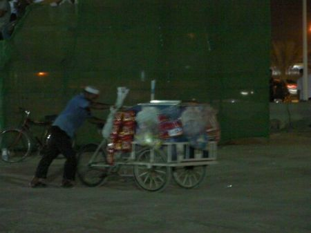 a man with a bicycle cart loaded with snack foods