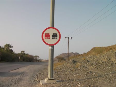 road sign with a red truck and a black truck