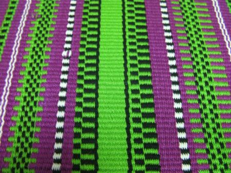 close up of magenta/green/white/black woven table runner