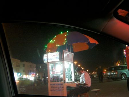 man sitting at a small booth under a large umbrella doing watch repair