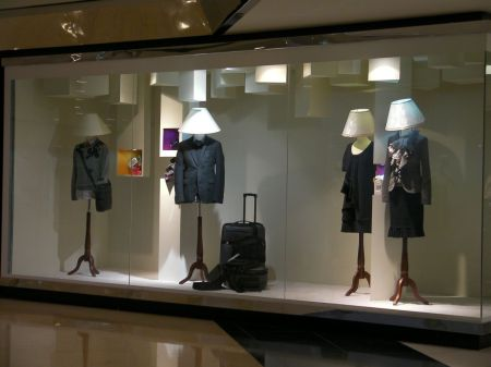 store display with manikins who have lampshades instead of heads.