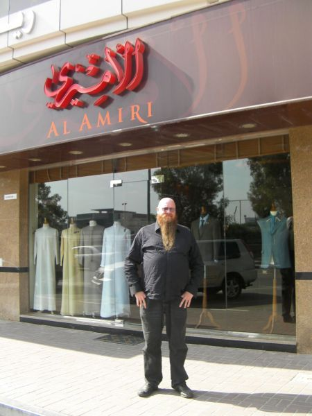 man in front of a tailor shop