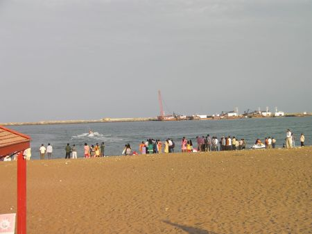 people lined up on the beach watching water skiers