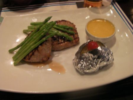 rectangular white plate with two pork cutlets, asparagus, baked potato, herb butter.