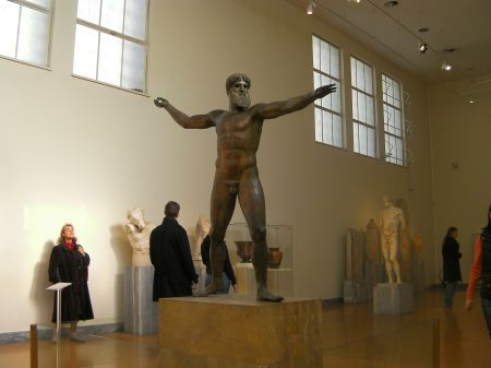 large bronze sculpture of Zeus posed as if he is throwing a lightning bolt