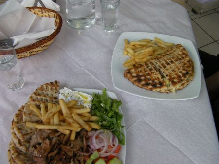 two plates full of grilled meat, fries, bread, salad