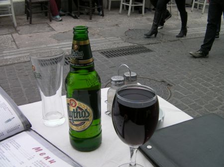 a bottle of Mythos beer and a full glass of red wine