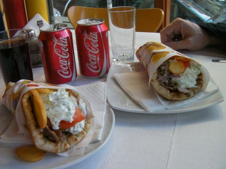two gyro sandwiches with two Coca Colas