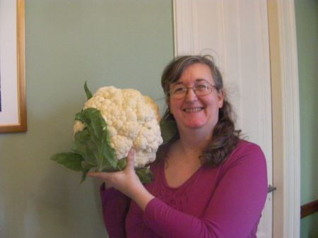 me holding the cauliflower next to my head, it is twice as large