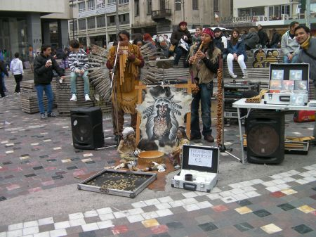 two pan flute musicians dressed like plains indians