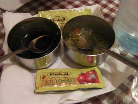 two metal bowls and ketchup packets