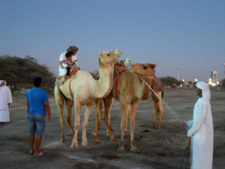 man and small boy riding a camel