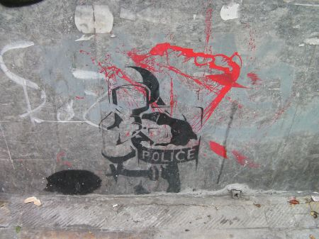 stencil of riot policeman pointing gun directly at the viewer