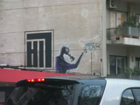 graffiti of a graffiti artist wearing a gas mask while painting the word fear