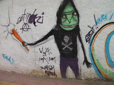 graffiti green faced guy wearing a skull and cross bones hoody carrying an orange club