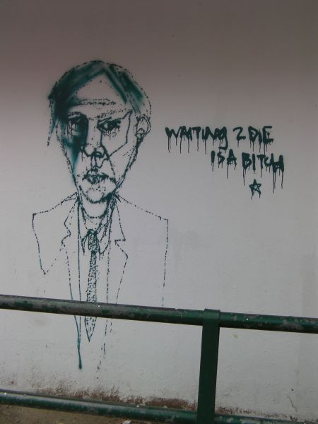graffiti of a man in a suit with caption waiting to die is a bitch