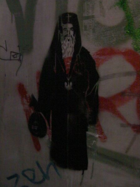 stenciled graffiti of a priest holding a bag of money and giving the finger