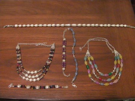 three necklaces and three bracelets, some with pearls, others with multicolored stones