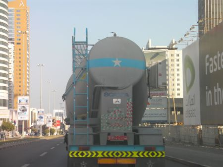 the back of a tanker truck with green and red stripe reflective tape on it